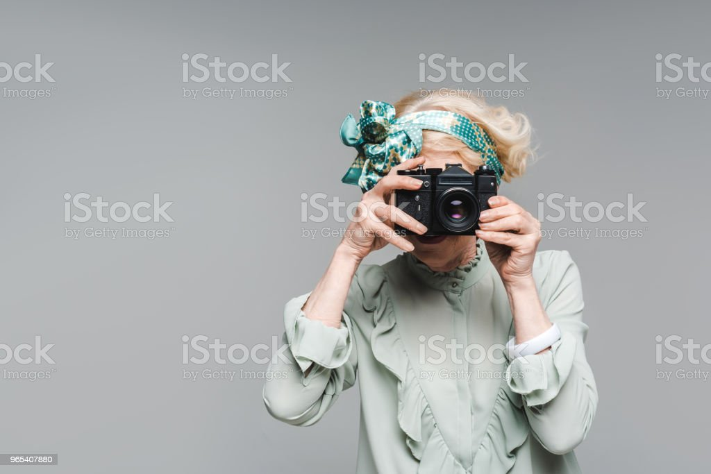 stylish senior woman taking photo with vintage film camera isolated on grey royalty-free stock photo
