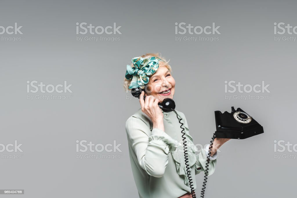 stylish senior woman talking by rotary phone isolated on grey zbiór zdjęć royalty-free