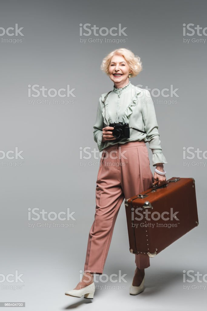 stylish senior woman walking with vintage suitcase and film camera on grey royalty-free stock photo