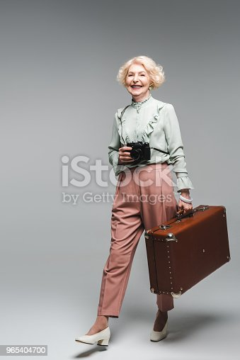 Stylish Senior Woman Walking With Vintage Suitcase And Film Camera On Grey Stock Photo & More Pictures of Adults Only
