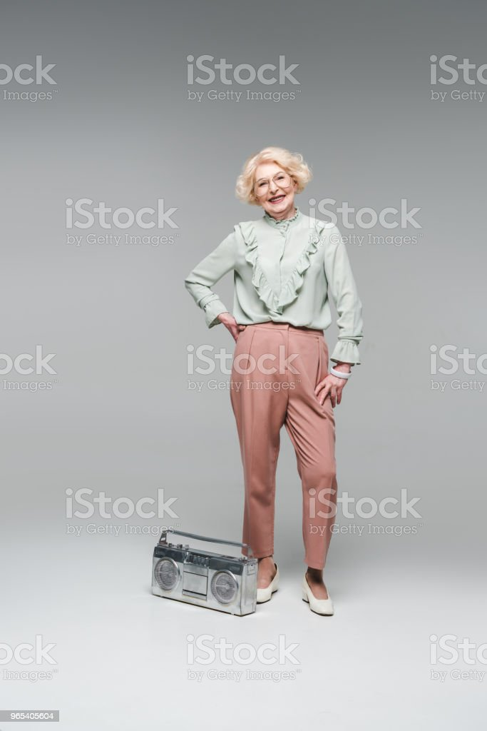 stylish senior woman with vintage boombox isolated on grey zbiór zdjęć royalty-free