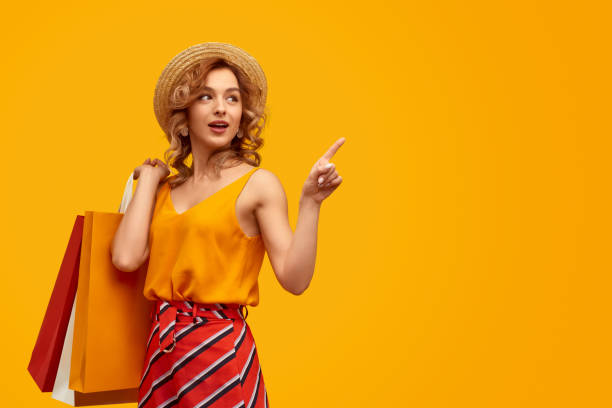 Stylish shopaholic with purchases pointing at empty space stock photo