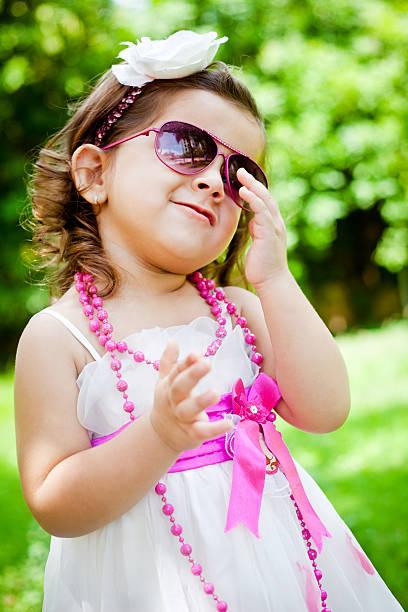 stilvolle kleine freudig indische mädchen outdoor-portrait - sonnenbrille kleinkind stock-fotos und bilder