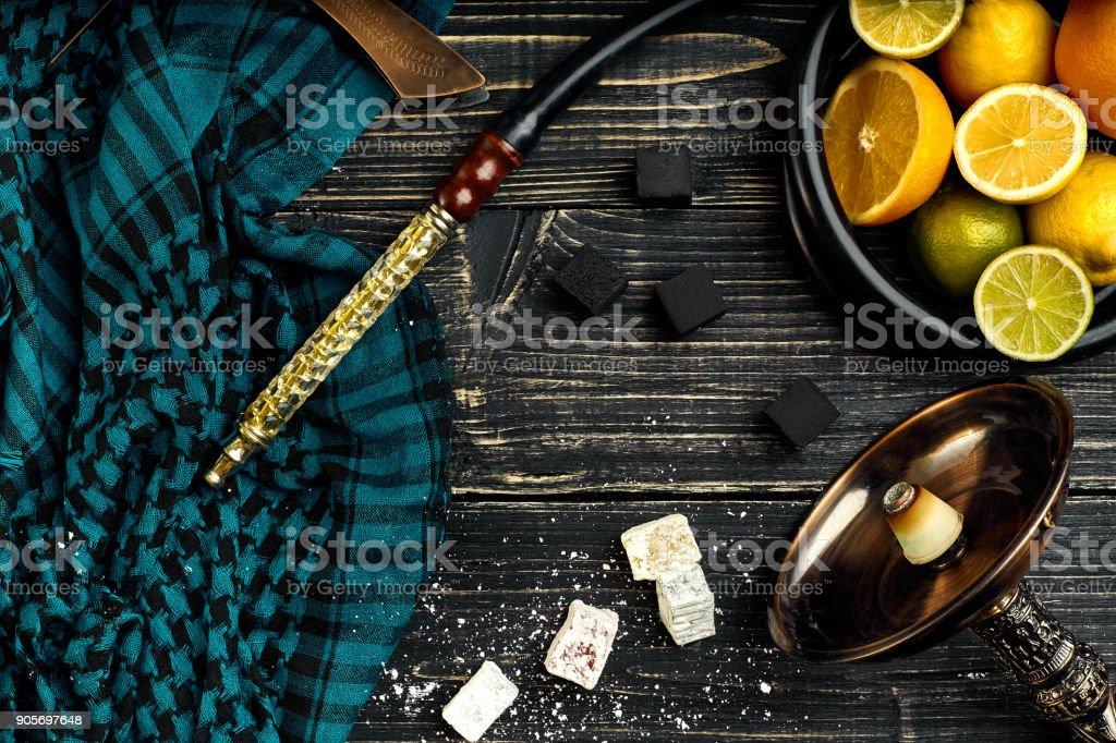 Stylish Smoking hookah and basket with lemon, lime and orange on stock photo