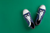 istock Stylish sneaker pen on a green background. Youth shoes. View from above. 1222417261
