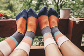 Stylish socks on couple legs and metal cup on wooden porch with view on woods in mountains. Happy family relaxing together, togetherness moment. Funny cute socks