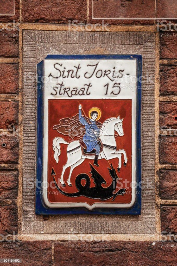 Stijlvol straat teken met geëmailleerde verf van Sint Joris en de draak, in de straat met de naam van de Heilige in's-Hertogenbosch. foto