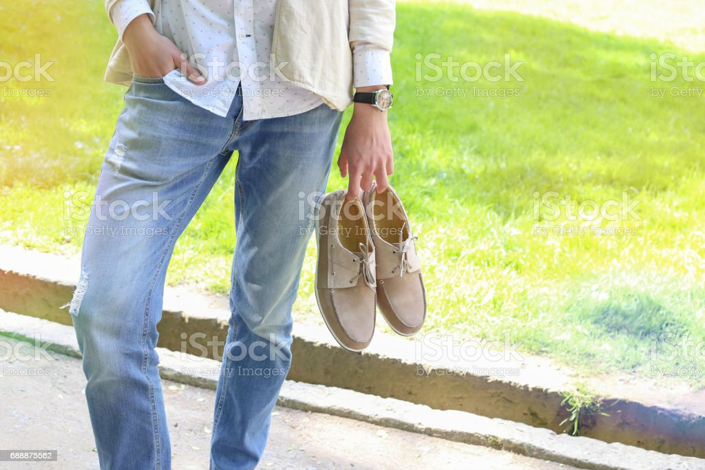 Stylish student with shoes in hands. stock photo