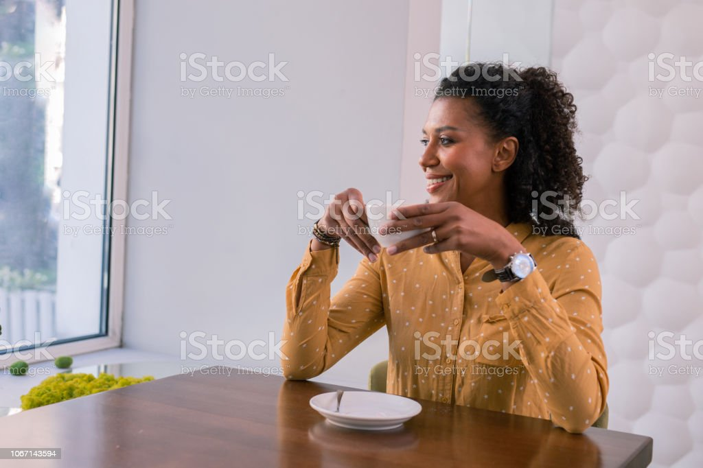 Coffee break. Stylish successful businesswoman wearing yellow spotted...