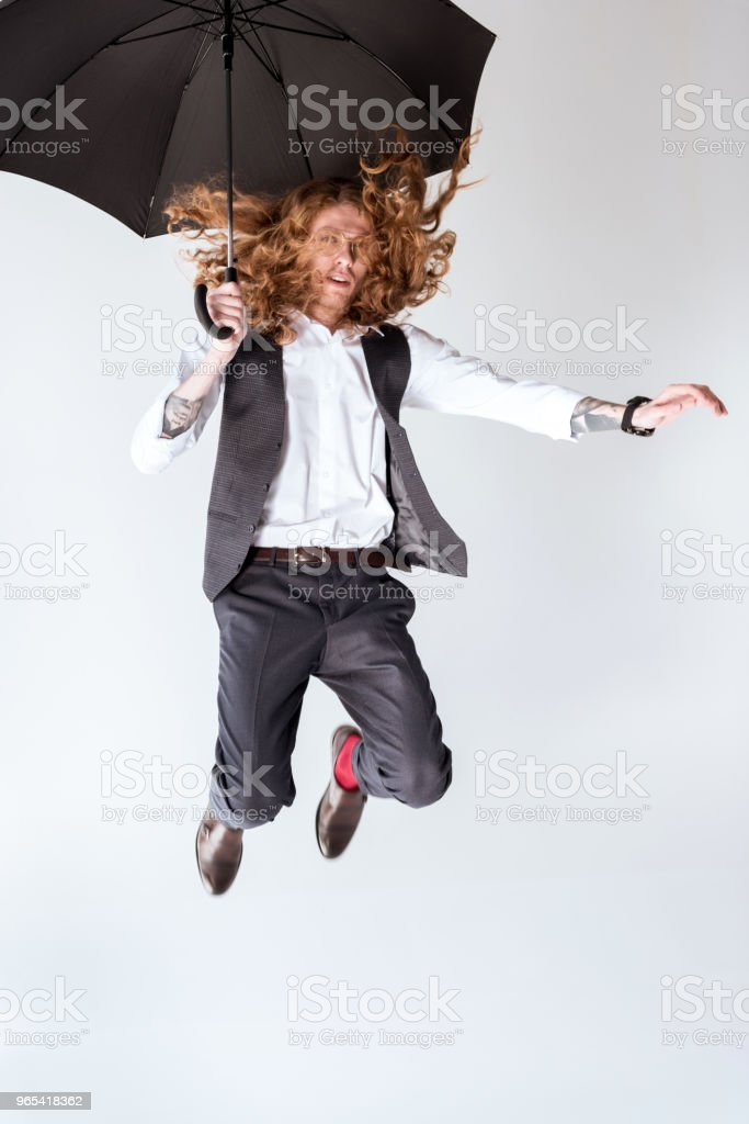 stylish tattooed businessman jumping against white background royalty-free stock photo
