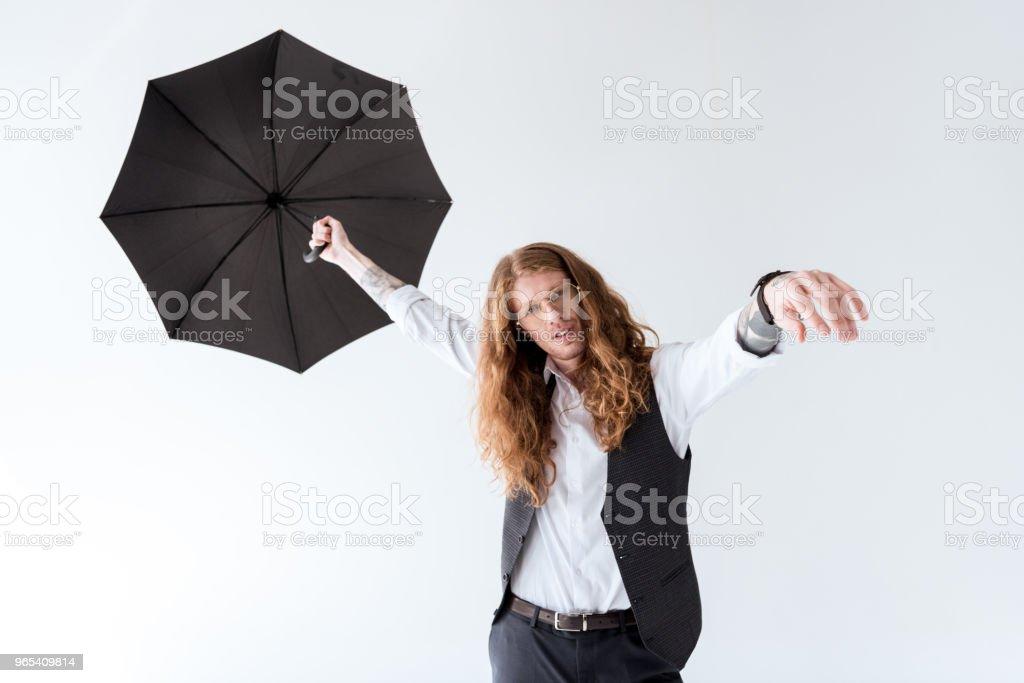 stylish tattooed businessman with curly hair having fun with black umbrella isolated on white zbiór zdjęć royalty-free