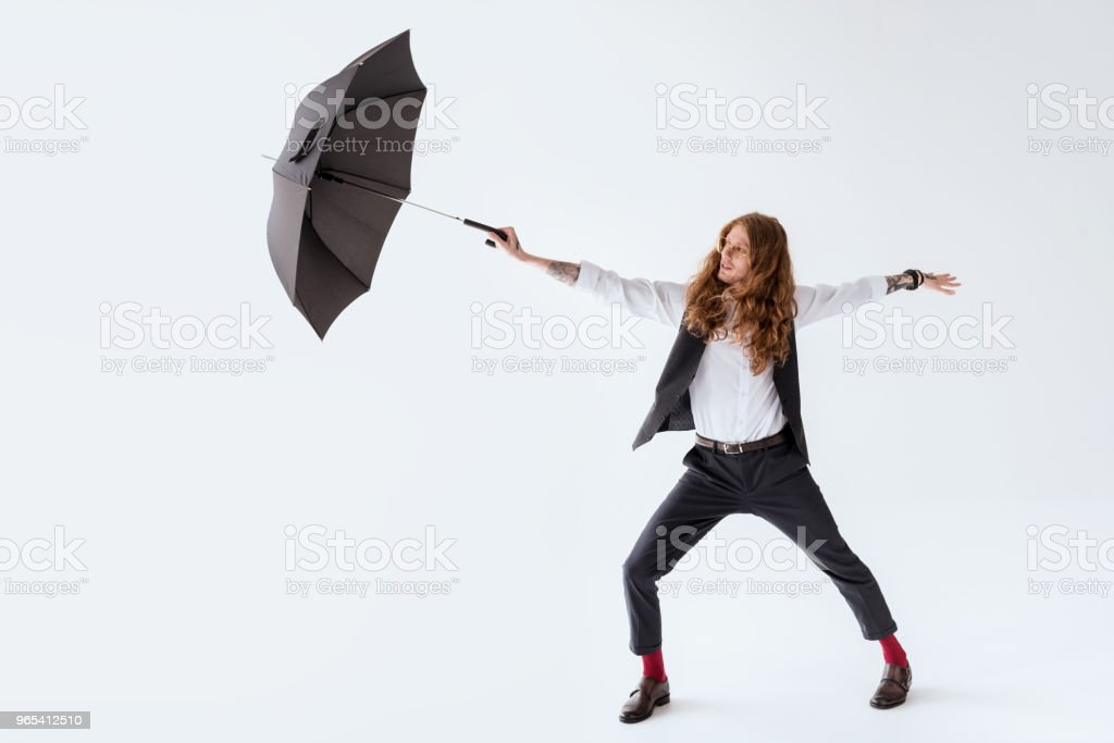 stylish tattooed businessman with curly hair having fun with black umbrella isolated on white royalty-free stock photo