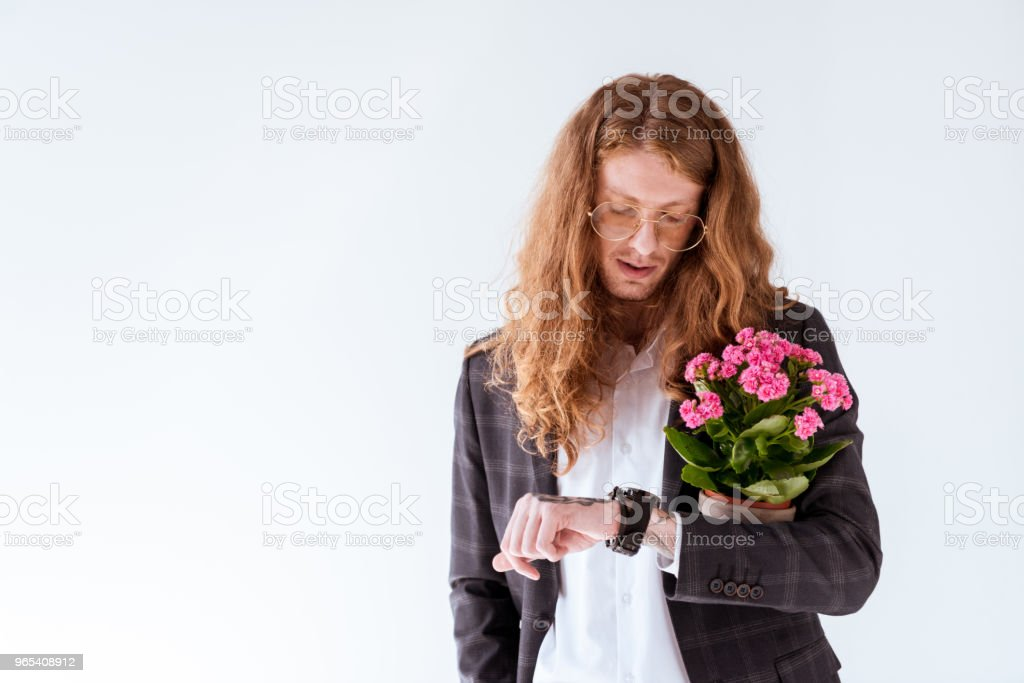 stylish tattooed businessman with curly hair holding potted flowers and checking time isolated on white royalty-free stock photo