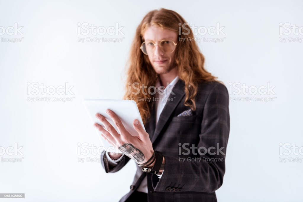 stylish tattooed businessman with curly hair holding tablet isolated on white royalty-free stock photo