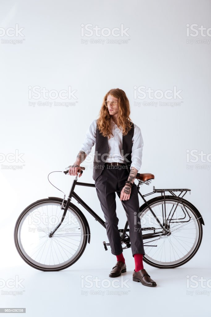 stylish tattooed businessman with curly hair leaning on bicycle and looking away royalty-free stock photo