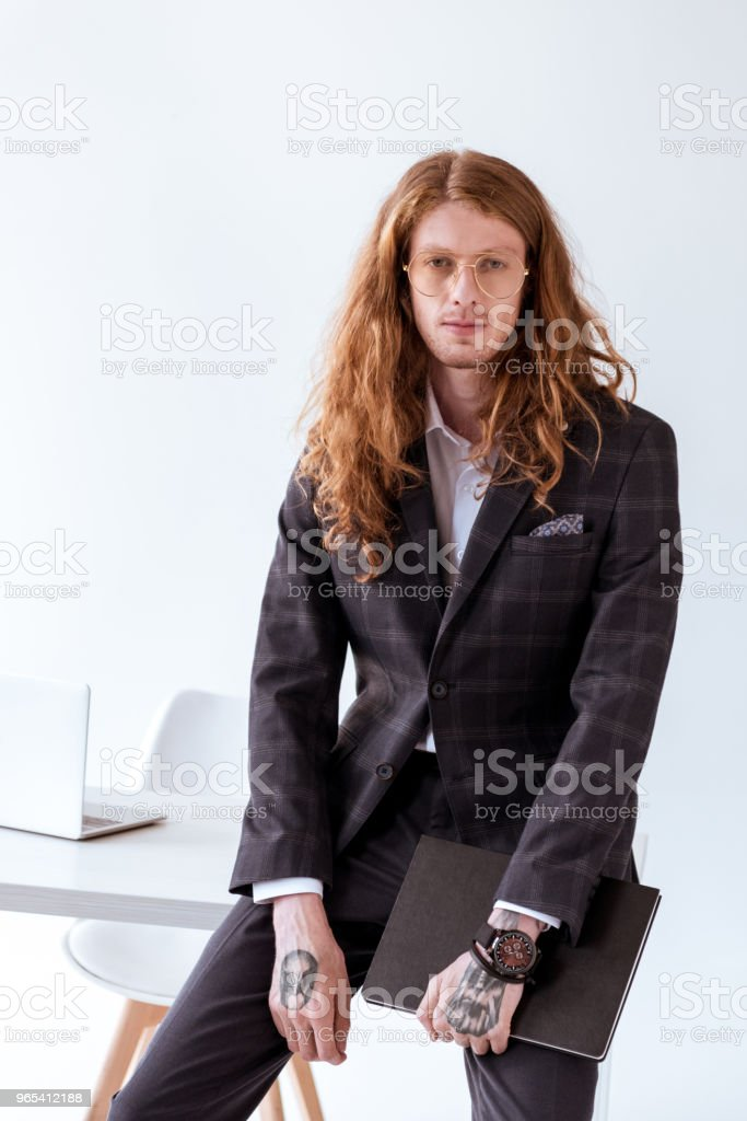 stylish tattooed businessman with curly hair leaning on table and holding folder - Zbiór zdjęć royalty-free (Biuro)