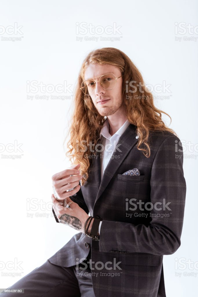 stylish tattooed businessman with curly hair looking at camera isolated on white zbiór zdjęć royalty-free