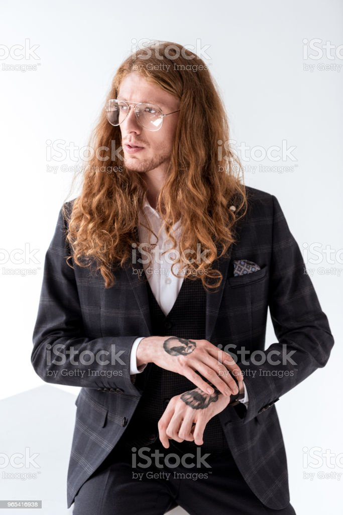 stylish tattooed businessman with curly hair looking away on white royalty-free stock photo