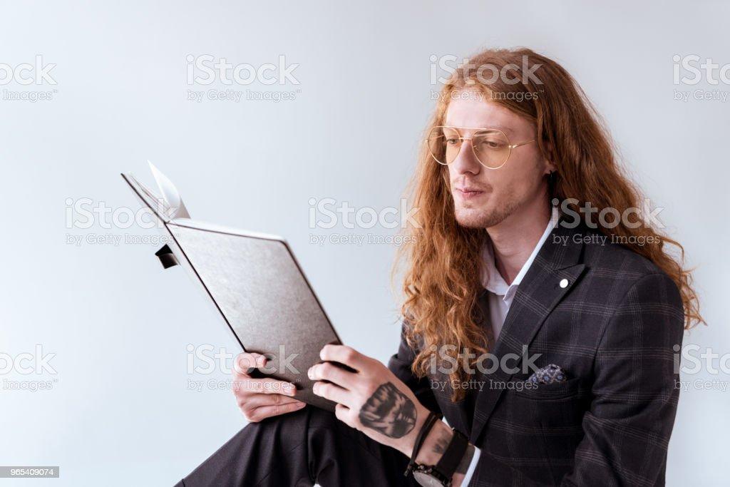 stilvolle tätowierte Geschäftsmann mit dem lockigen Haar, Lesen von Dokumenten - Lizenzfrei Anzug Stock-Foto
