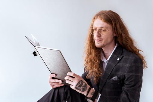 곱슬 머리 문서를 읽는 세련 된 문신된 사업가 경영자에 대한 스톡 사진 및 기타 이미지
