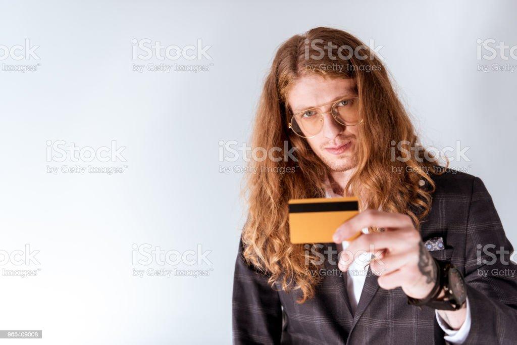 élégant tatoué homme d'affaires avec carte de crédit montrant les cheveux bouclés - Photo de A la mode libre de droits