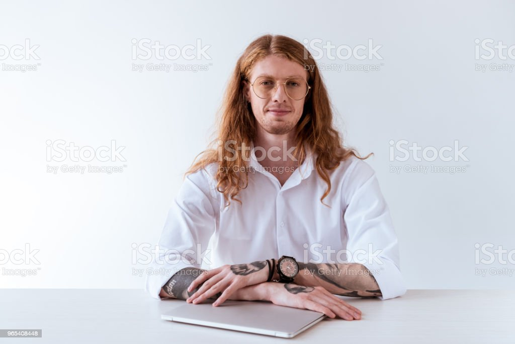 stylish tattooed businessman with curly hair sitting at table with laptop and looking at camera isolated on white royalty-free stock photo