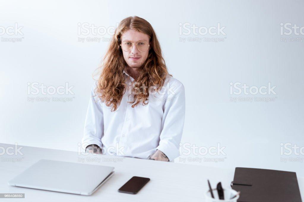 élégant homme tatoué aux cheveux bouclés, assis à table avec ordinateur portable et smartphone - Photo de A la mode libre de droits