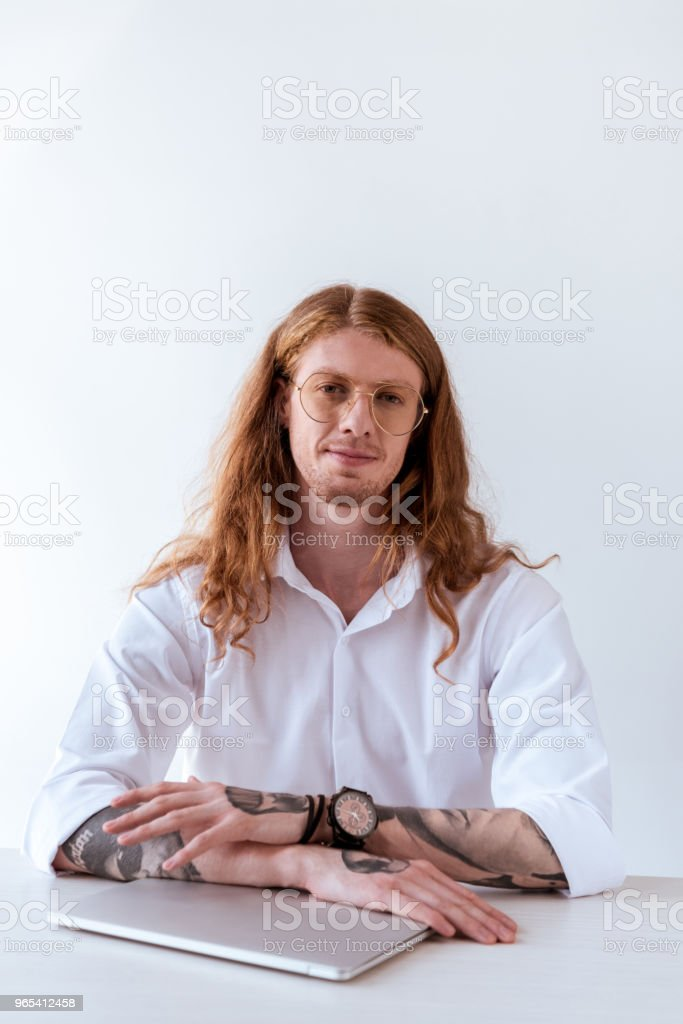 stylish tattooed businessman with curly hair sitting at table with laptop and looking at camera zbiór zdjęć royalty-free