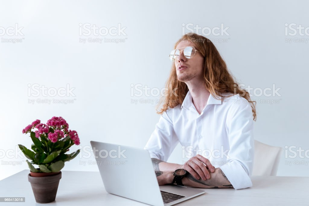 stylish tattooed businessman with curly hair sitting at table with laptop and looking up zbiór zdjęć royalty-free