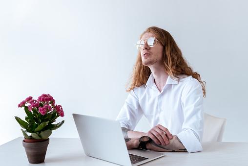 노트북 테이블에 앉아서 올려 곱슬 머리로 세련 된 문신된 사업가 경영자에 대한 스톡 사진 및 기타 이미지