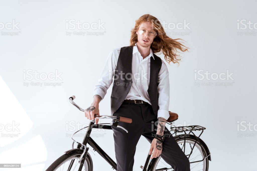 stylish tattooed businessman with curly hair sitting on bicycle and looking at camera zbiór zdjęć royalty-free