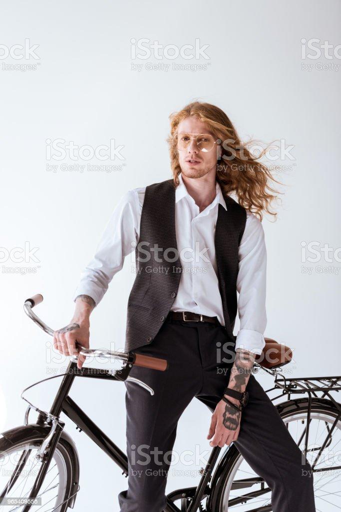 chic homme tatoué avec des cheveux frisés, assis sur le vélo isolé sur blanc - Photo de A la mode libre de droits