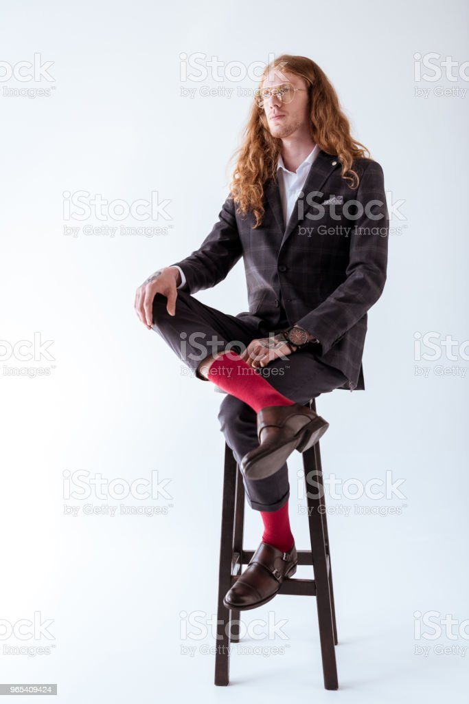 stylish tattooed businessman with curly hair sitting on chair isolated on white zbiór zdjęć royalty-free