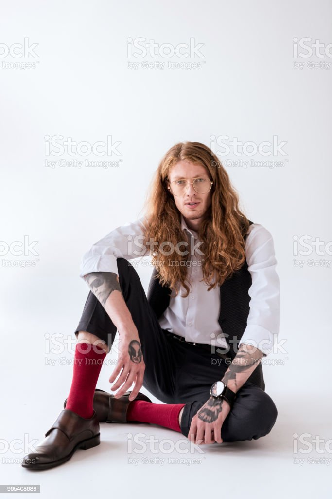 stylish tattooed businessman with curly hair sitting on floor and looking at camera on white zbiór zdjęć royalty-free