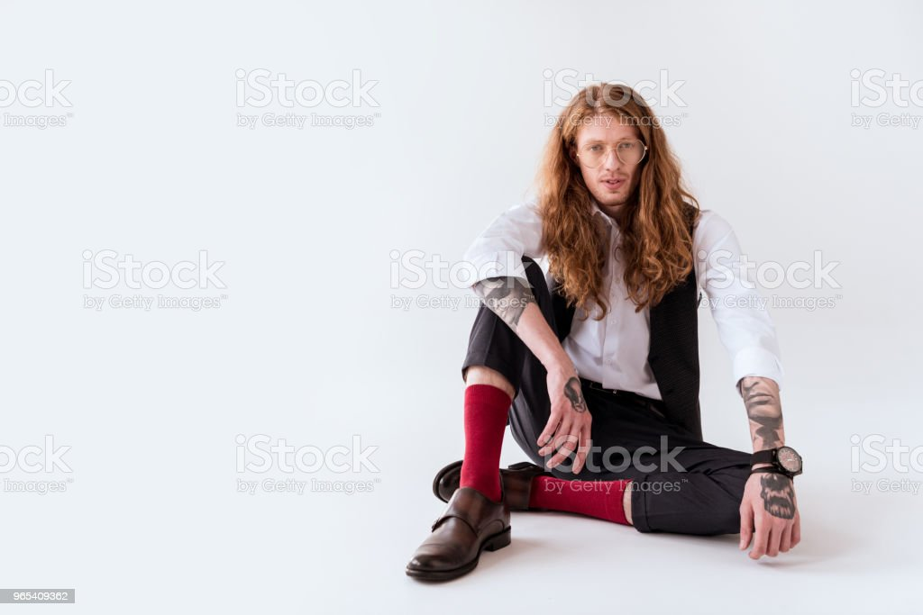 stylish tattooed businessman with curly hair sitting on floor on white royalty-free stock photo
