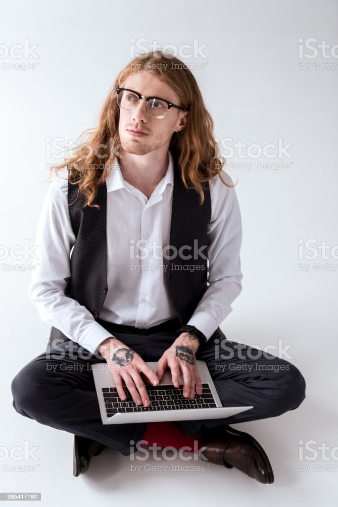 stylish tattooed businessman with curly hair sitting on floor with laptop royalty-free stock photo