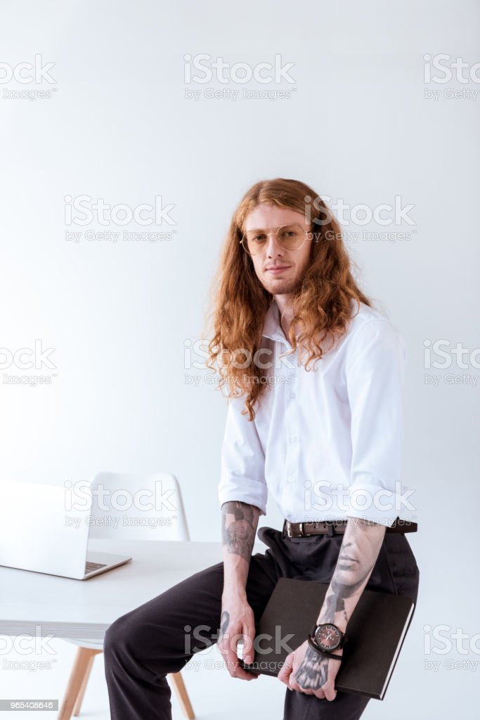 stylish tattooed businessman with curly hair sitting on table and looking at camera in office royalty-free stock photo