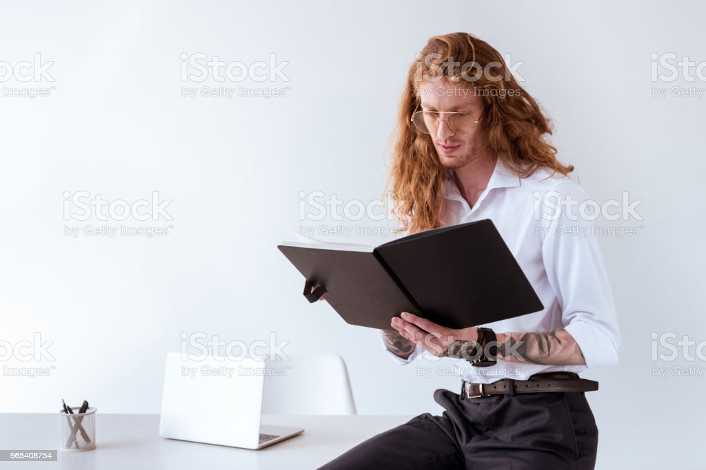 stylish tattooed businessman with curly hair sitting on table and reading documents in workplace royalty-free stock photo