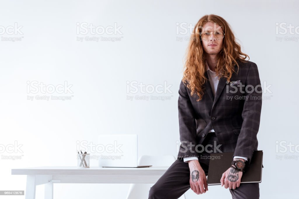 stylish tattooed businessman with curly hair sitting on table and holding folder zbiór zdjęć royalty-free
