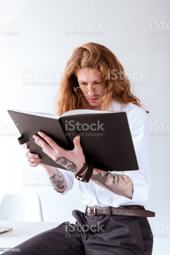 stylish tattooed businessman with curly hair sitting on table and reading documents in workspace royalty-free stock photo