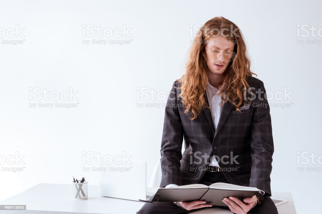 stylish tattooed businessman with curly hair sitting on table and reading documents in folder royalty-free stock photo