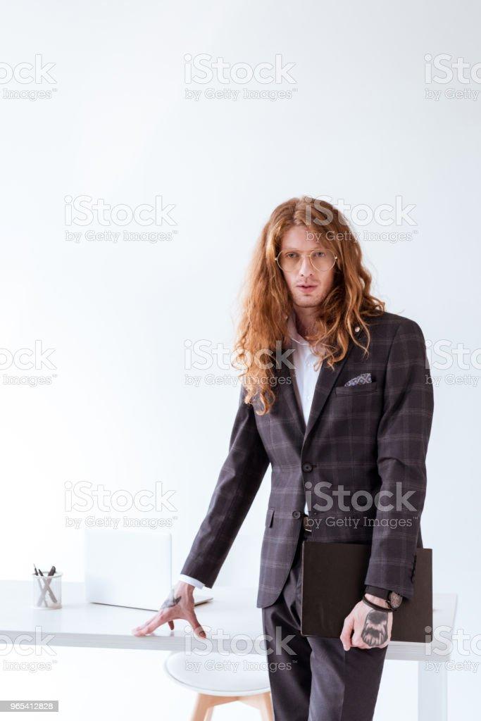 stylish tattooed businessman with curly hair standing near table and holding folder zbiór zdjęć royalty-free