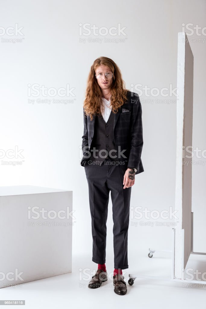stylish tattooed businessman with curly hair standing near white cube royalty-free stock photo