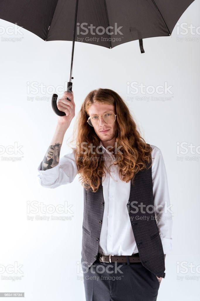 stylish tattooed businessman with curly hair standing under black umbrella isolated on white zbiór zdjęć royalty-free