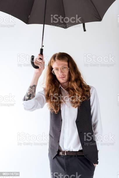 흰색 절연 검은 우산 아래에서 곱슬 머리 서와 함께 세련 된 문신된 사업가 개인 장식품에 대한 스톡 사진 및 기타 이미지