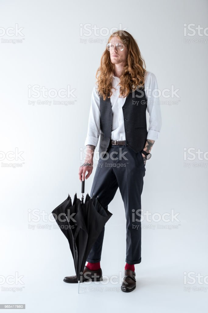 stylish tattooed businessman with curly hair standing with black umbrella and looking away zbiór zdjęć royalty-free