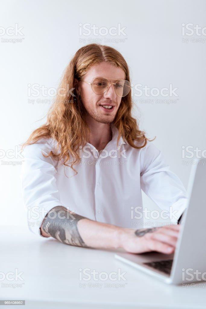 stylish tattooed businessman with curly hair working with laptop in office zbiór zdjęć royalty-free