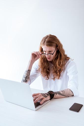 사무실에서 노트북으로 작업 하 고 만지고 안경 곱슬 머리와 세련 된 문신된 사업가 경영자에 대한 스톡 사진 및 기타 이미지