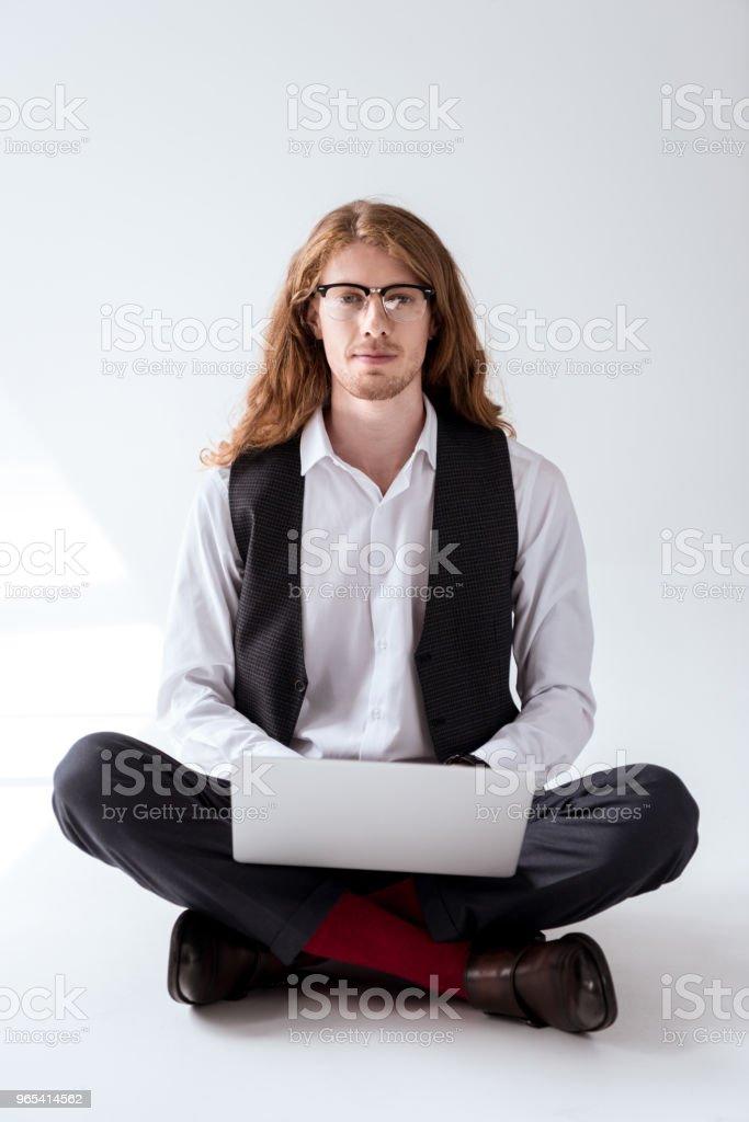 élégant homme tatoué avec des cheveux roux, assis sur le plancher avec ordinateur portable - Photo de A la mode libre de droits