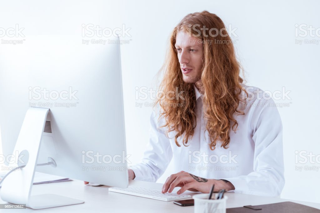 stylish tattooed businessman with ginger long hair working with computer in workspace zbiór zdjęć royalty-free